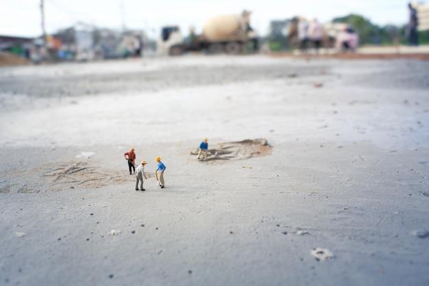 Pracownicy budowlani (miniaturowi) na betonowej podłodze. płytka głębia kompozycji pola i kolor vintage.