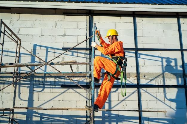 Pracownicy budowlani noszący linę bezpieczeństwa podczas pracy na budowie.