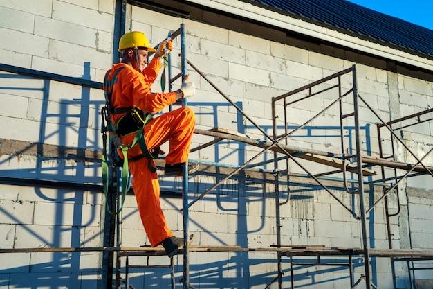 Pracownicy budowlani noszący szelki bezpieczeństwa podczas pracy na wysokości