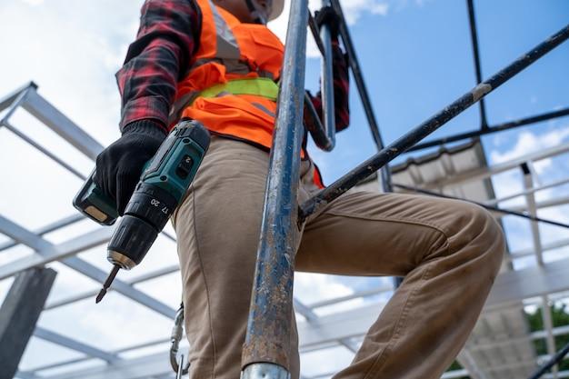Pracownicy budowlani noszący szelki bezpieczeństwa pracujący na wysokim poziomie na placu budowy, narzędzia dekarskie, wiertarka elektryczna używana na nowych dachach z blachą.