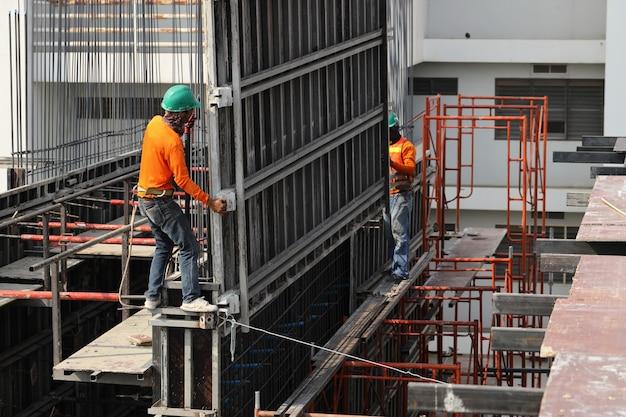 Pracownicy budowlani pracują przy wysokich budynkach, aby budować budynki.