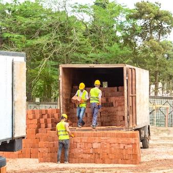 Pracownicy budowlani rozładowujący cegły