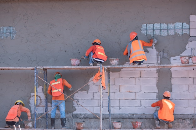 Pracownicy budowlani tynkują ścianę budynku i belkę za pomocą cementowej mieszanki tynku cementowego i piasku na placu budowy