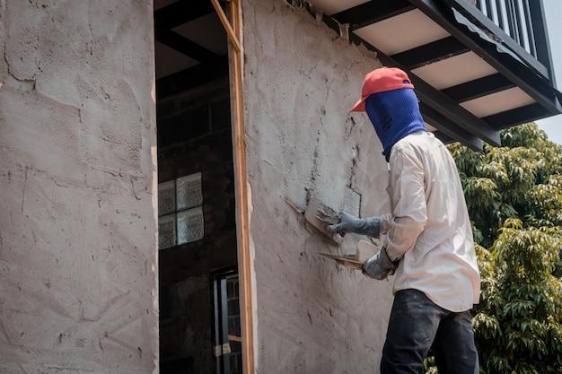 Pracownicy budowlani tynkujący ścianę budynku za pomocą tynku cementowego