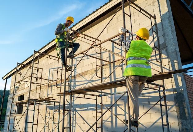 Pracownicy budowlani w wyposażeniu mundurowym i ochronnym pracujący na rusztowaniach na placu budowy