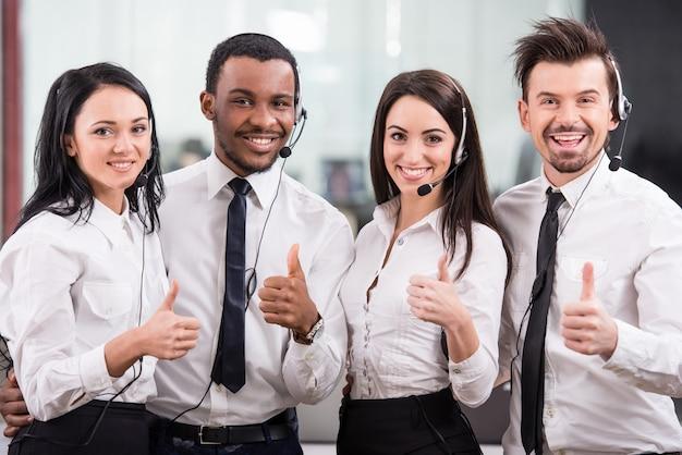 Pracownicy call center są uśmiechnięci i patrząc na kamery.