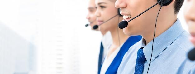 Pracownicy centrum telefonicznego rozmawiają przez telefon z przyjaznym i pomocnym nastawieniem