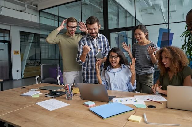 Pracownicy cieszą się z sukcesu transakcji w biurze