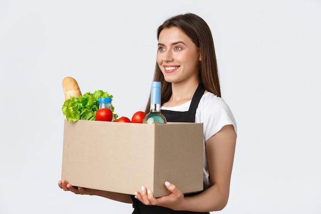 Pracownicy, dostawy i zamówienia online, koncepcja sklepów spożywczych. profil ładnej uroczej sprzedawczyni, kasjerki w czarnym fartuchu trzymającej pudełko z artykułami spożywczymi, jedzeniem i napojami, obsługującej zamówienie do klienta
