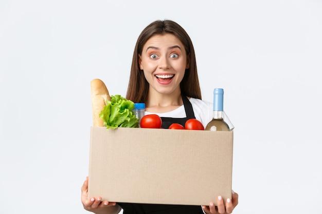 Pracownicy, dostawy i zamówienia online, koncepcja sklepów spożywczych. przyjazna, sympatyczna młoda sprzedawczyni trzymająca pudełko z artykułami spożywczymi, uśmiechnięta radośnie do klienta