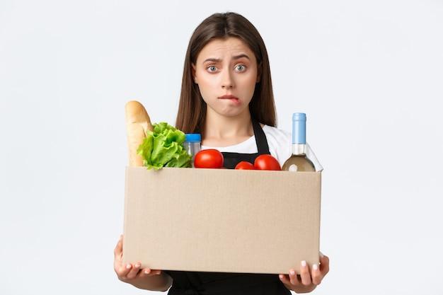 Pracownicy, dostawy i zamówienia online, koncepcja sklepów spożywczych. zdziwiona i niezdecydowana urocza sprzedawczyni, kasjerka trzymająca pudełko z zamówieniem klienta, kurierka przynosi zakupy online do domu klienta