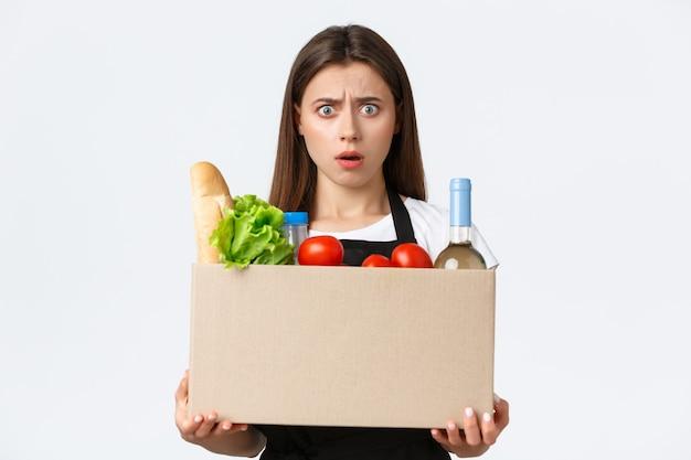 Pracownicy, dostawy i zamówienia online, koncepcja sklepów spożywczych. zszokowana i zdezorientowana kasjerka, sprzedawczyni trzymająca paczkę towarów, pudełko z zakupami i marszcząca brwi sfrustrowana