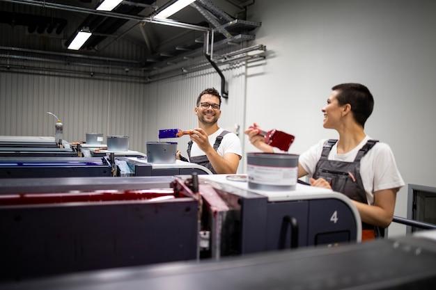 Pracownicy drukarni dodają więcej farby do maszyny drukarskiej.