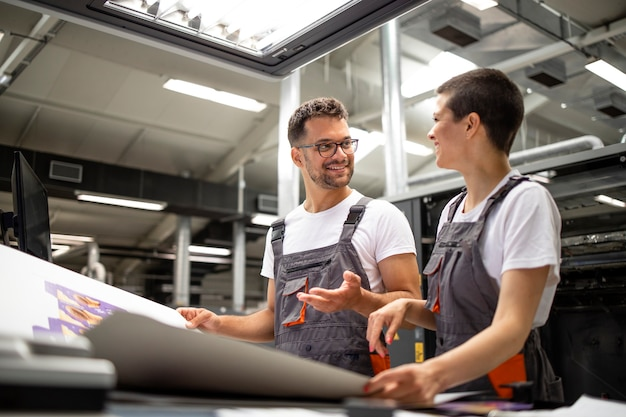 Pracownicy drukarni rozmawiają o jakości druku w fabryce produkcyjnej.