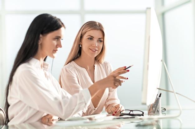 Pracownicy dyskutują o czymś siedząc przy biurowym stole