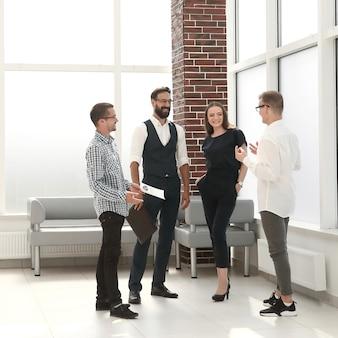 Pracownicy dyskutują o nowych pomysłach, stojąc w holu biura.