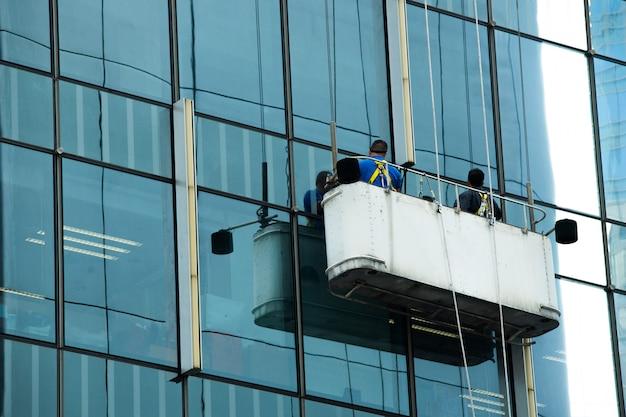 Pracownicy dźwigu kołyski czyste okna szklane wysokiego budynku