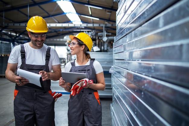 Pracownicy fabryki chodzą po zakładzie przemysłowym i dyskutują o wydajności produkcji