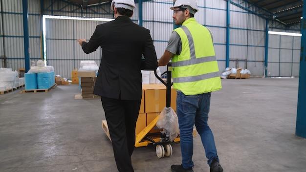 Pracownicy fabryki dostarczają paczki na wózku pchającym w magazynie. koncepcja zarządzania łańcuchem dostaw przemysłu.