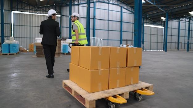Pracownicy fabryki dostarczają paczki na wózku pchającym w magazynie