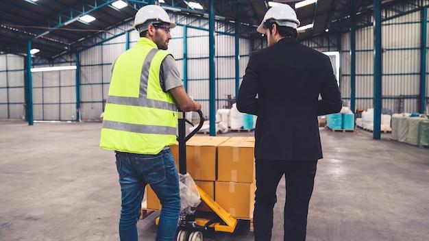 Pracownicy fabryki dostarczają paczki na wózku pchającym w magazynie.