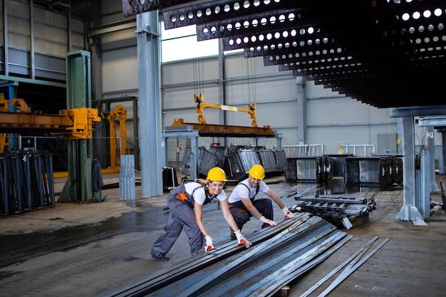 Pracownicy fabryki obsługujący razem części metalowe