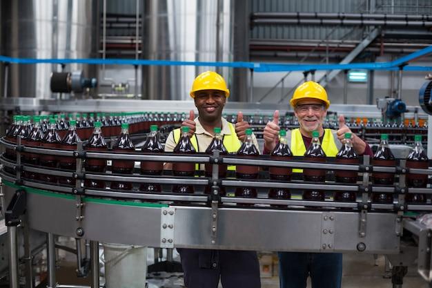 Pracownicy fabryki pokazujący kciuki do góry na linii do produkcji napojów