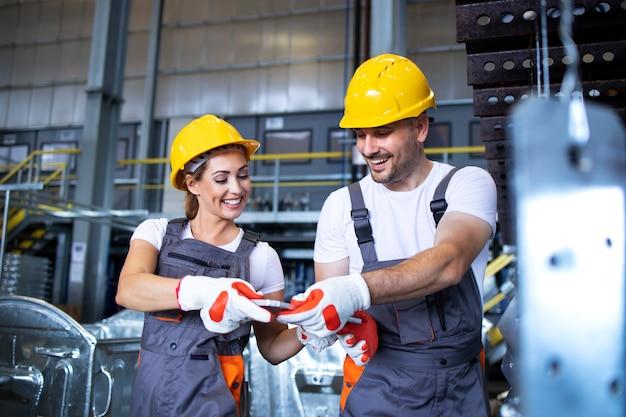 Pracownicy fabryki pracujący razem w przemysłowej linii do produkcji metalu
