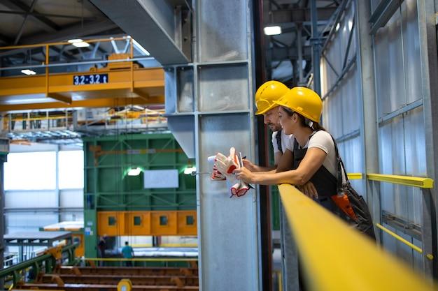 Pracownicy fabryki rozmawiają w hali produkcyjnej