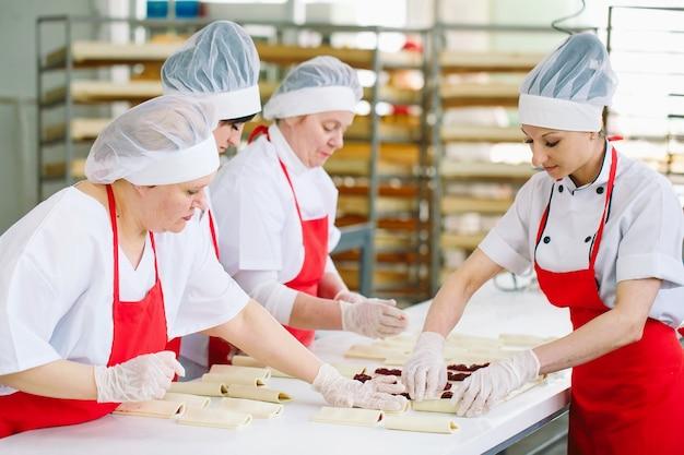Pracownicy fabryki słodyczy przygotowują desery z nadzieniem