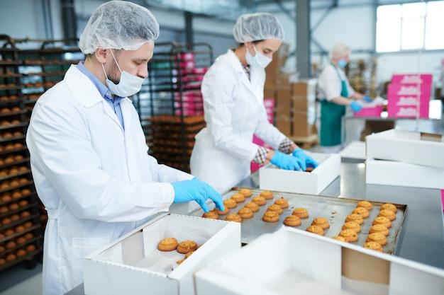 Pracownicy fabryki słodyczy wkładający ciasto do pudeł
