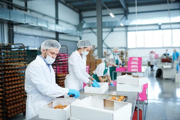 Pracownicy fabryki słodyczy wkładający ciasto do skrzynek