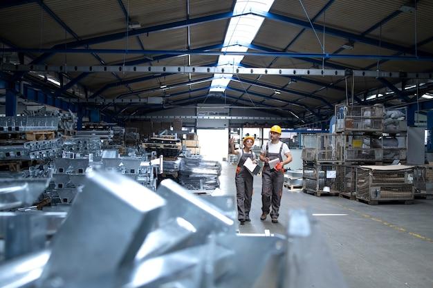 Pracownicy fabryki w przemysłowej hali produkcyjnej