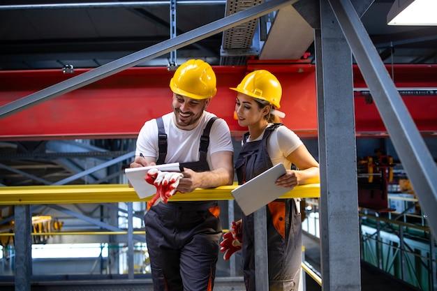 Pracownicy fabryki w sprzęcie ochronnym stoją na hali i dzielą się pomysłami