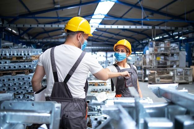 Pracownicy fabryki witają się łokciami podczas pandemii wirusa koronowego