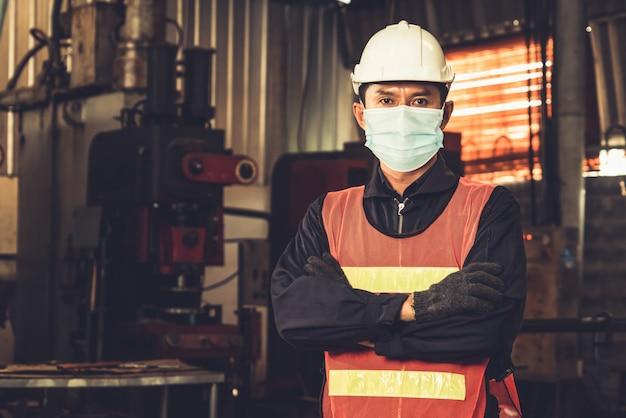 Pracownicy fabryki z maską na twarz chronią przed wybuchem coronavirus covid-19