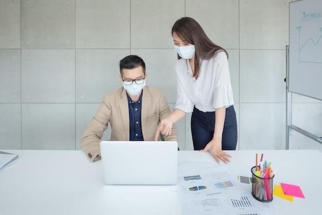 Pracownicy firm noszący maski podczas pracy w biurze, aby zachować higienę, przestrzegają polityki firmy. zapobiegawczo w okresie epidemii koronawirusa lub covid19.