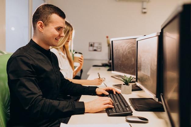 Pracownicy firmy informatycznej pracujący na komputerze