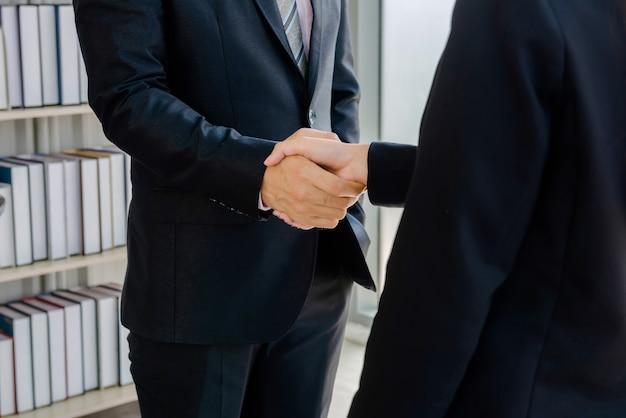Pracownicy firmy podają sobie ręce