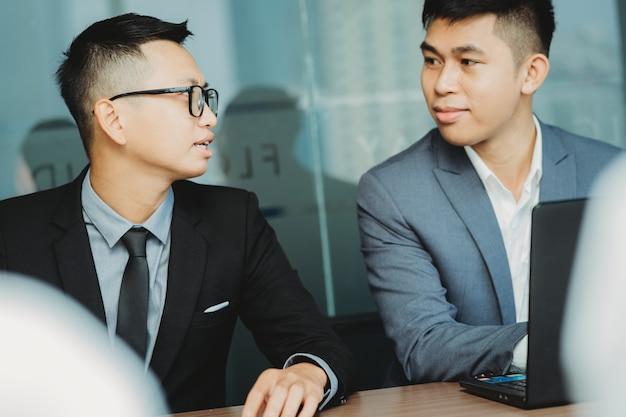 Pracownicy firmy rozmawiają z kolegami w pobliżu podczas spotkania