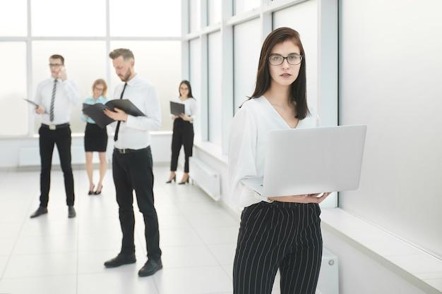 Pracownicy firmy stojący w przestronnym lobby biurowym. zdjęcie z miejscem na kopię