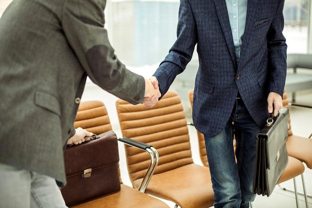 Pracownicy firmy z teczkami ściskającymi ręce w holu nowoczesnego biura
