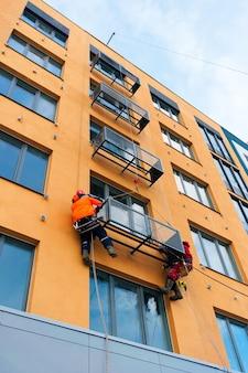 Pracownicy instalują nisze na klimatyzatory w budowanym domu
