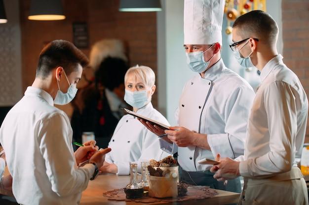 Pracownicy kawiarni na porannej odprawie w maskach ochronnych