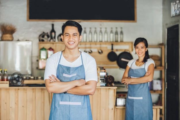 Pracownicy kawiarni stojący ze skrzyżowanymi rękami