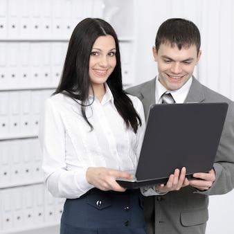 Pracownicy komunikujący się w internecie za pomocą laptopa.