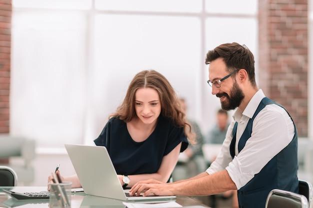 Pracownicy korzystający z laptopa do pracy z danymi finansowymi. ludzie i technologia