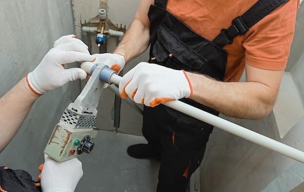 Pracownicy lutują rury ścienne do wbudowanego prysznica