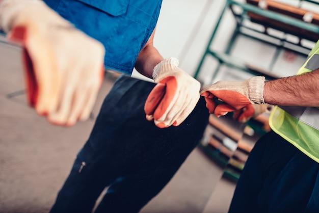 Pracownicy magazynu przewożący fabrycznie blachę ze stali nierdzewnej inox