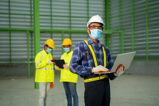 Pracownicy magazynu używający laptopa do sprawdzania konstrukcji